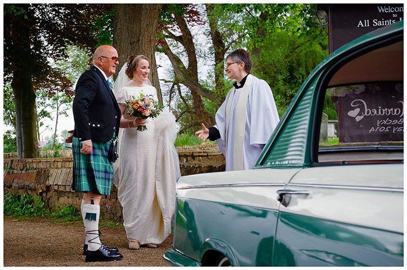bride and father greeted by vicar at All Saints Church Hartford