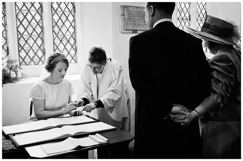 bride signs register as groom and his mother watch holding hands