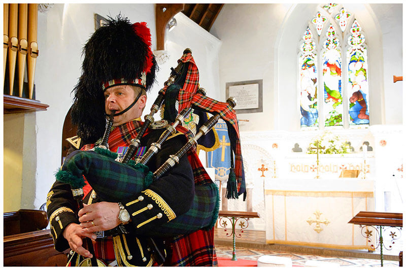 Scottish bag piper in church during wedding ceremony