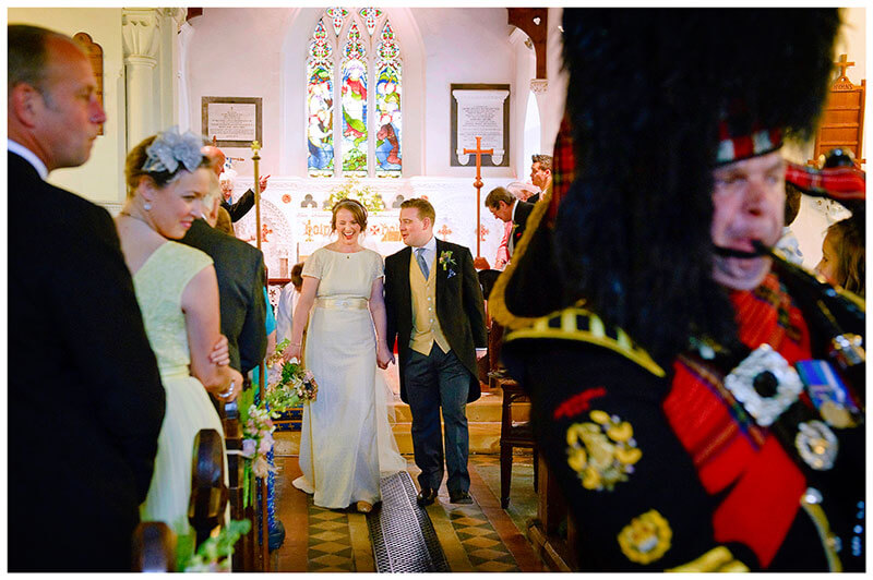 bagpiper leads the way out of church for the newly married couple