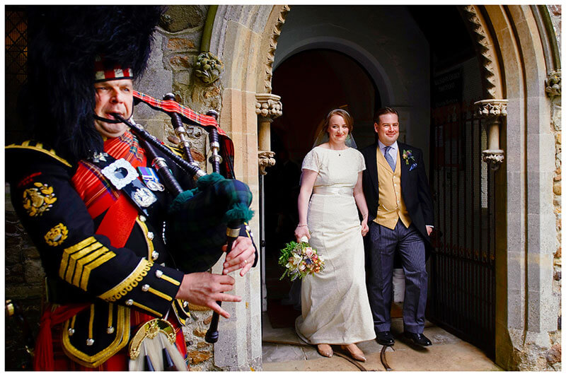 bride and groom leave church to scottish bagpiper