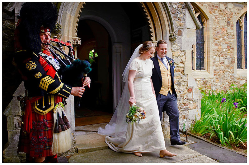 scottish bagpiper plays as couple leave All Saints Church Hartford