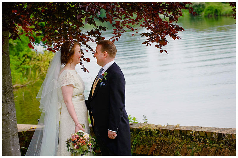 wedding couple enjoy moment near river under tree