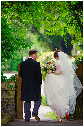 bride and groom walking away showing brides red sole shoes