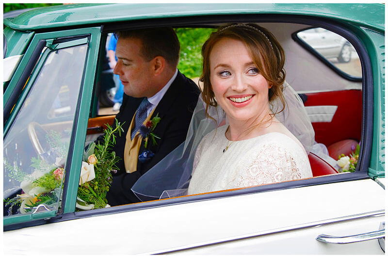 smiling bride looking out of car window