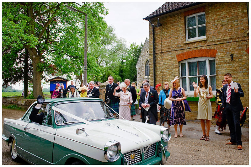 All Saints Church Hartford wedding guests wave bride groom off in small classic Triump Herald