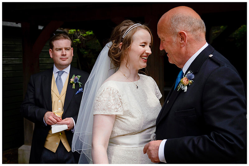 bride smiling at father as groom looks on