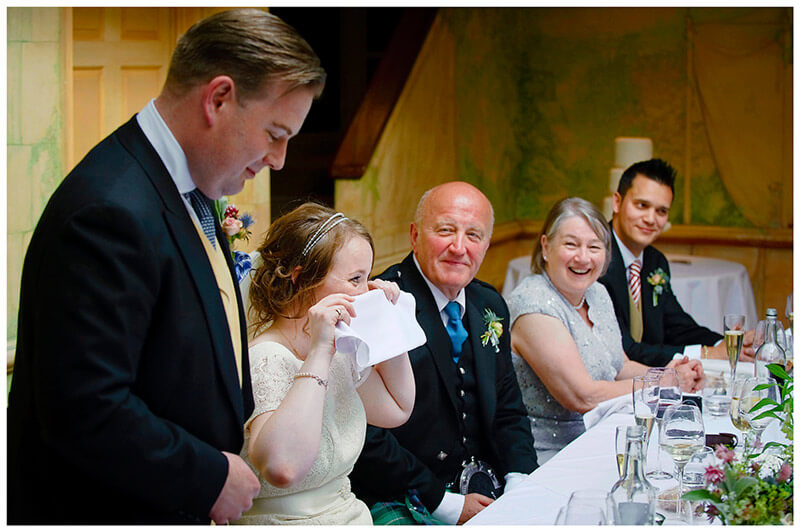 bride hides behind napkin during grooms speech