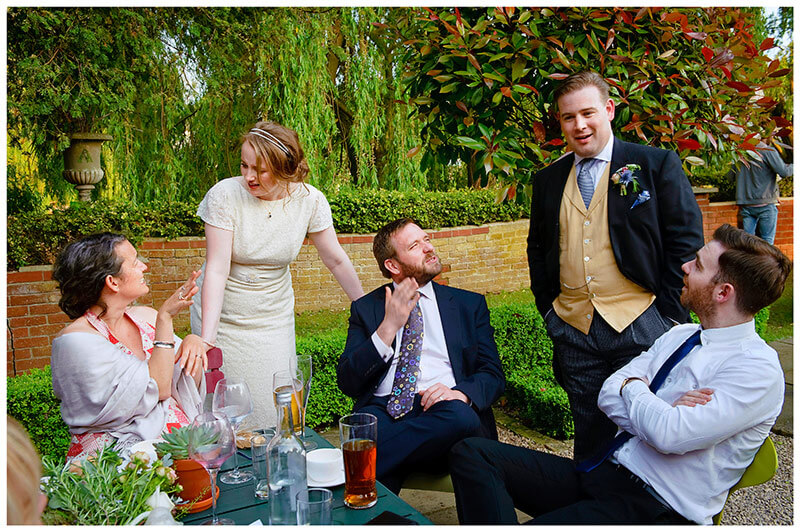Bride groom talking to sitting guests outside