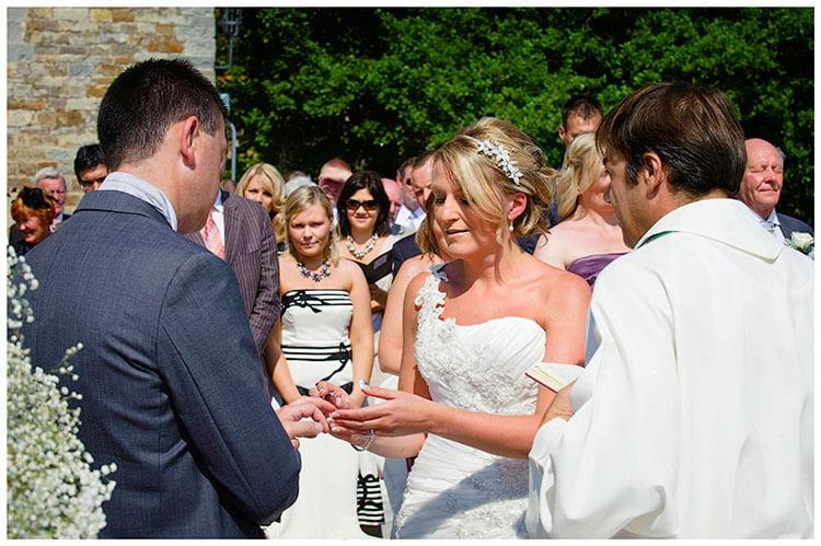 Castello di Vincigliata wedding bride places ring on grooms finger
