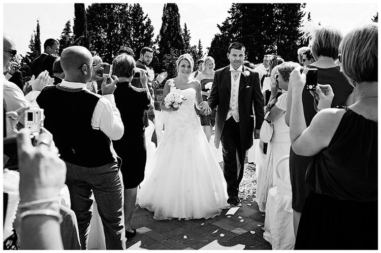 Castello di Vincigliata wedding guests take photos as couple walk down aisle