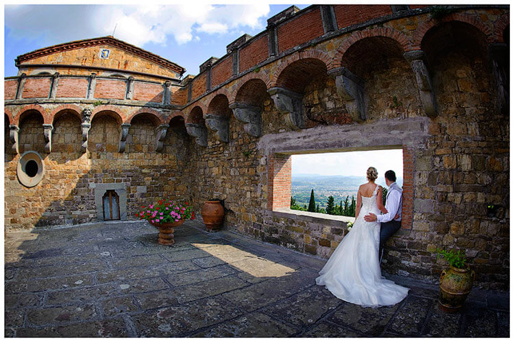 Castello di Vincigliata wedding bride groom looking out over Florence from castle tower