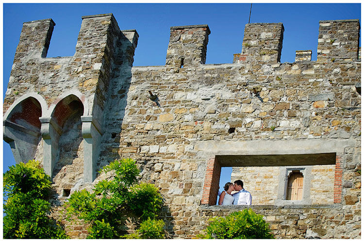 Castello di Vincigliata wedding bride groom kiss in castle tower opening