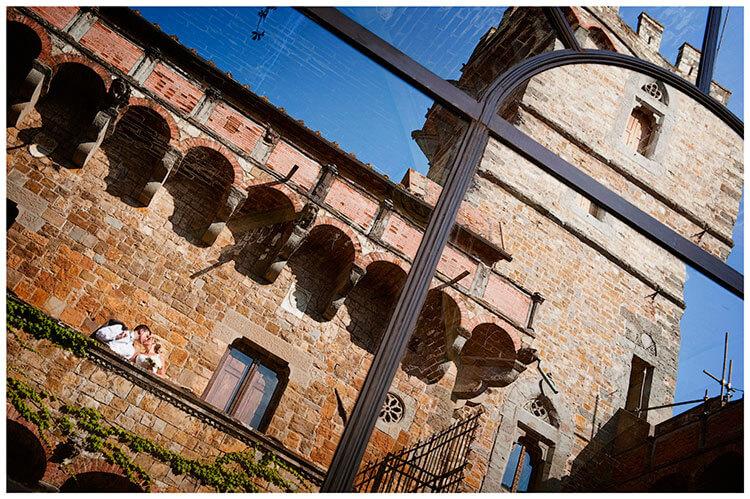 Castello di Vincigliata wedding bride groom kiss castle turret reflected in window