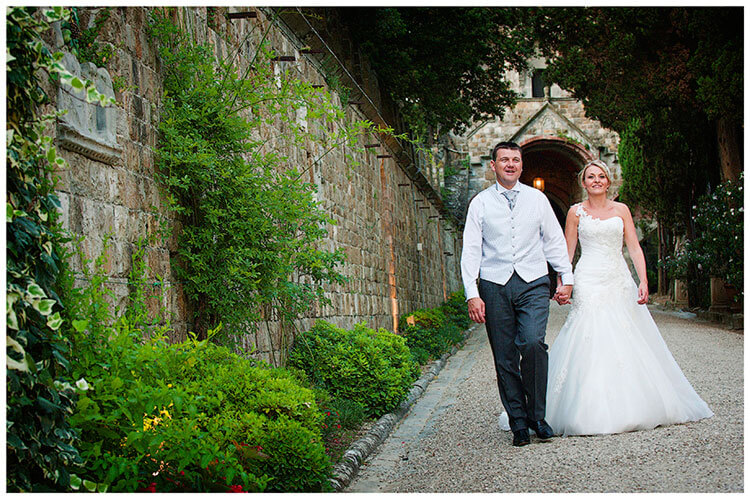 Castello di Vincigliata wedding bride groom walking hand in hand smiling