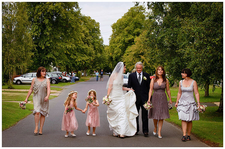 Childerley Hall Summer Wedding bride and bridesmaids walking with father down centre road