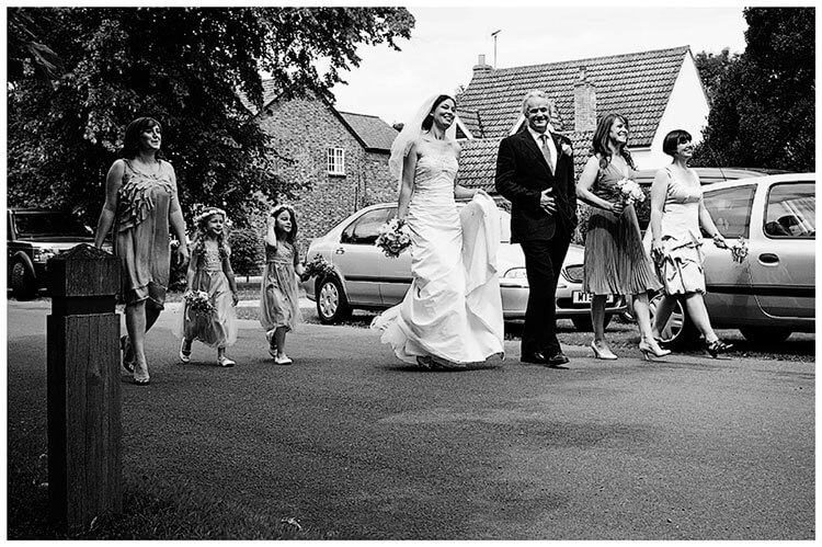 Childerley Hall Summer Wedding bridal party walking down road to church