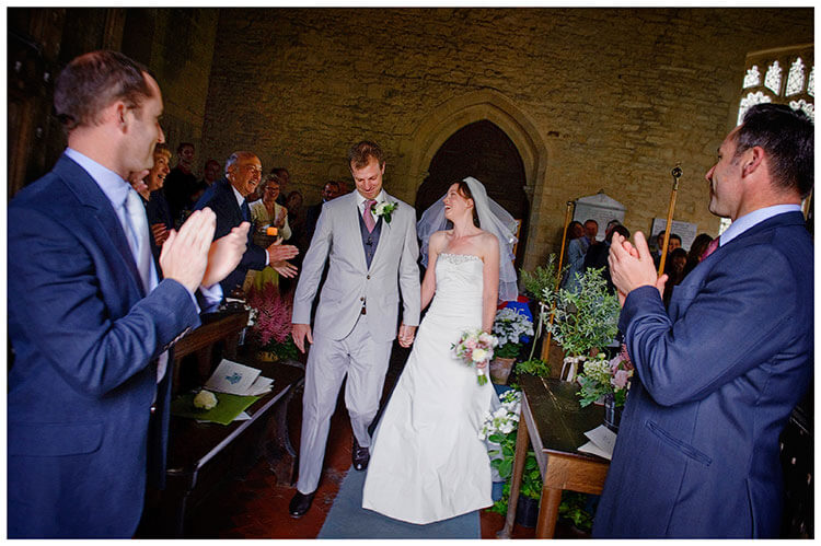 Childerley Hall Summer Wedding smiling couple applauded by guests as they walk down aisle