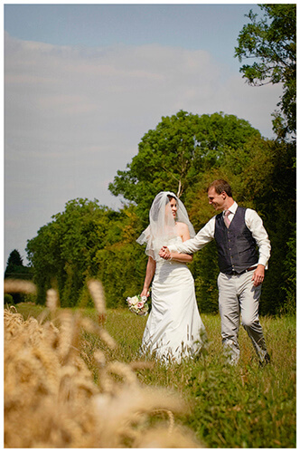 Childerley Hall Summer Wedding walking in barley field