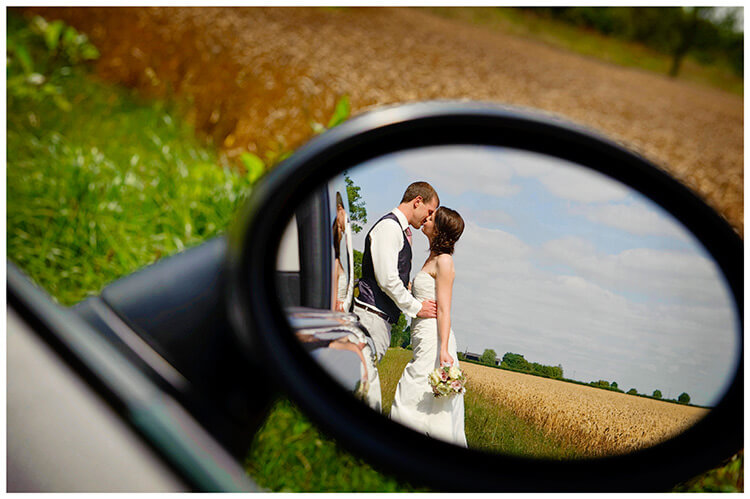 Childerley Hall Summer Wedding kiss reflection in car wing mirror