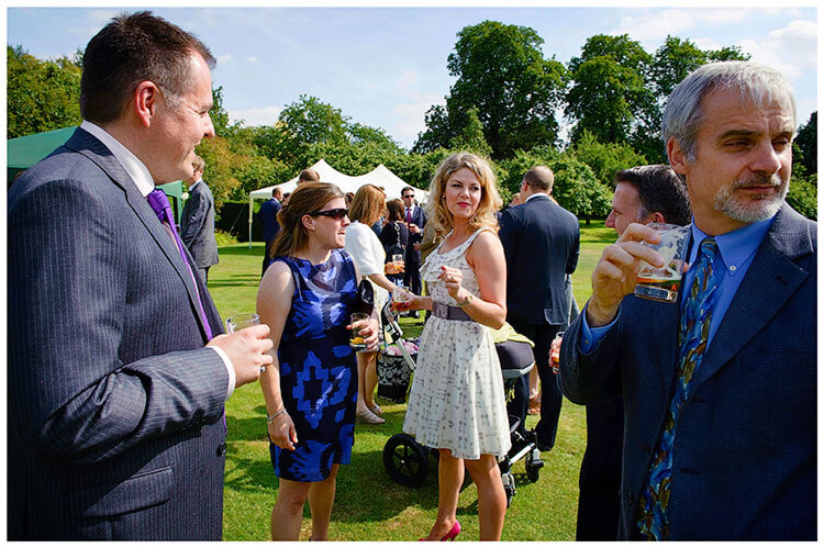 Childerley Hall Summer Wedding guests in conversation and enjoying drinks in sunshine