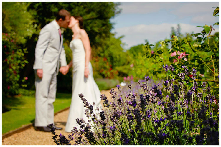 Childerley Hall Summer Wedding bride groom kiss next to lavender