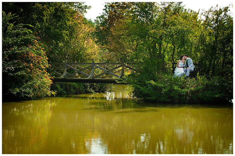 Childerley Hall Summer Wedding bride groom sat on bench near water and bridge