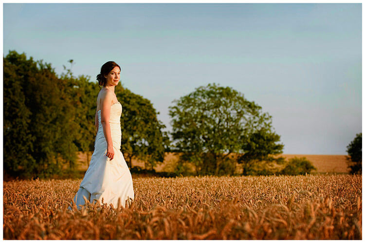 Childerley Hall Summer Wedding bride walking through barley field late evening