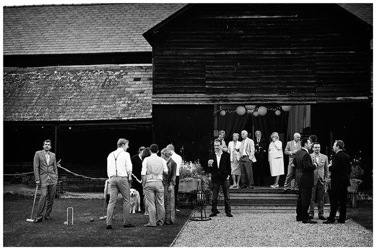 Guests enjoy drinks outside barn at Childerley Hall Summer Wedding