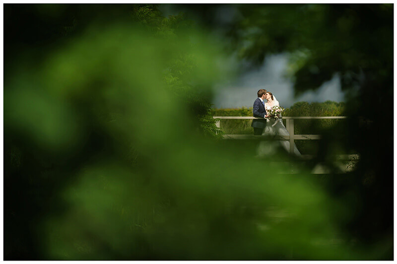 Friars Court Wedding Venue Oxfordshire bride groom kiss on bridge viewed through bushes