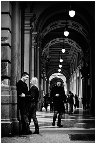 Pre-Wedding Photography in Florence couple embrace in portico as people pass