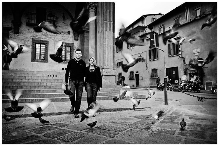 Pre-Wedding Photography in Florence couple walking through pigeons in flight