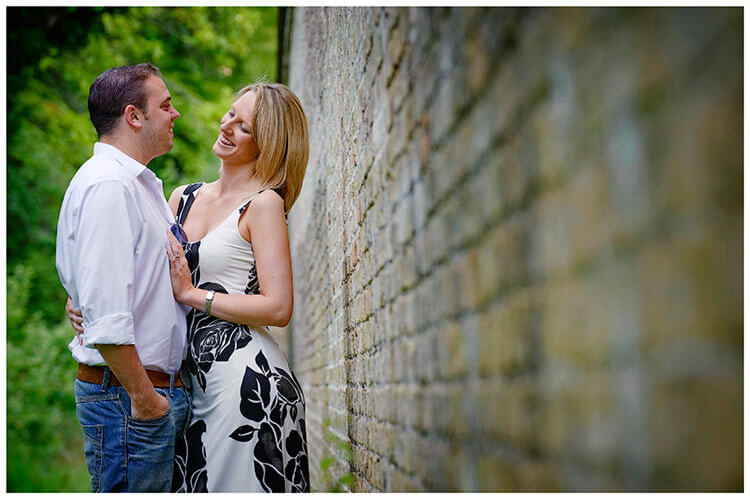Pre-Wedding Photography shoot in Cambridgeshire couple laugh during embrace next to old wall