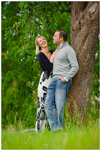 Pre-Wedding Photography shoot in Cambridgeshire laughing couple leaning against tree
