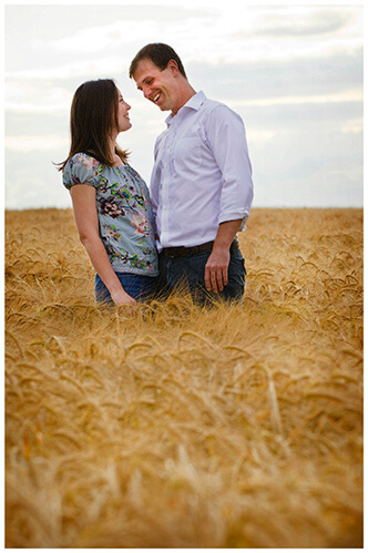 Pre-Wedding Shoot Leighton Bromswold happy smiling couple standing in barley field