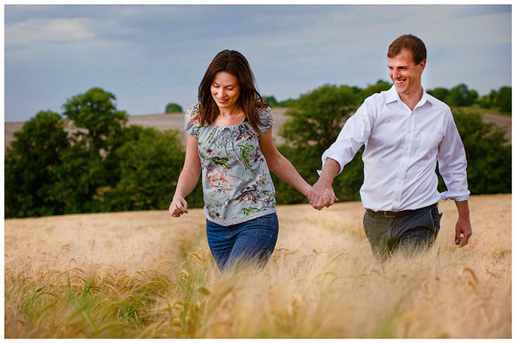 Pre-Wedding Shoot Leighton Bromswold smiling couple holding hands walking through barley filed