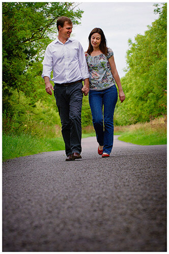 Pre-Wedding Shoot Leighton Bromswold happy couple walking along country road holding hands