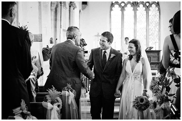 vintage Style Wedding Cambridgeshire groom shakes brides fathers hand as he walks down aisle with his new bride