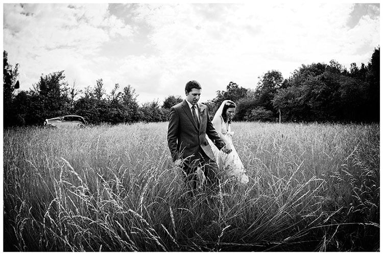 vintage Style Wedding couple walking through long grass wedding car in background