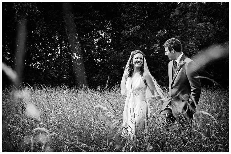 vintage Style Wedding happy smiling couple walking through long grass