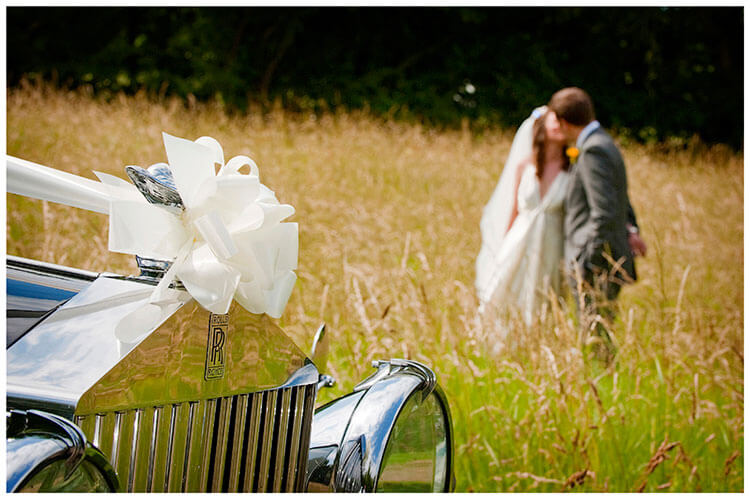 vintage Style Wedding car ribbon couple kissing in bcakground