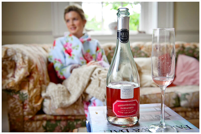 bride in dressing gown drinking rose wine
