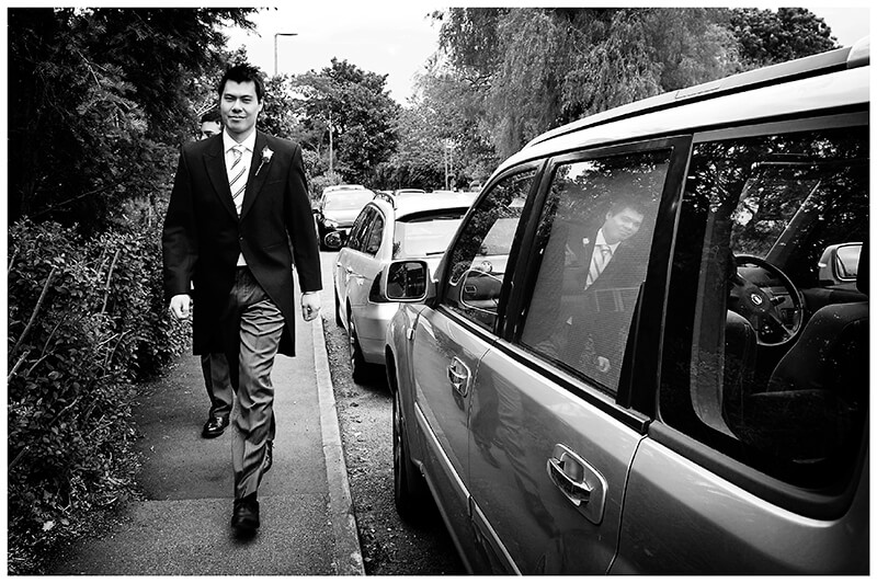 groom walking beside car reflected in window on way to church for the ceremony