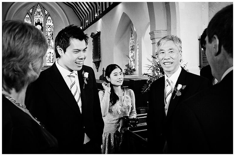 groom greeting guests with father in church