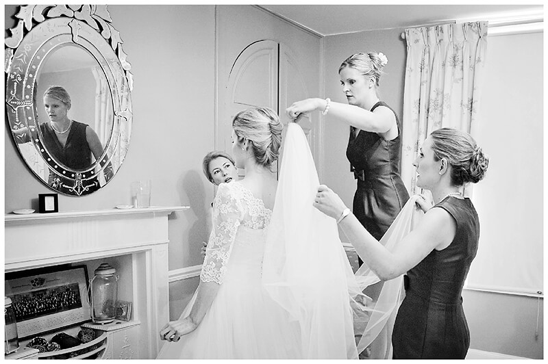brides maids placing veil on brides head while standing on chair