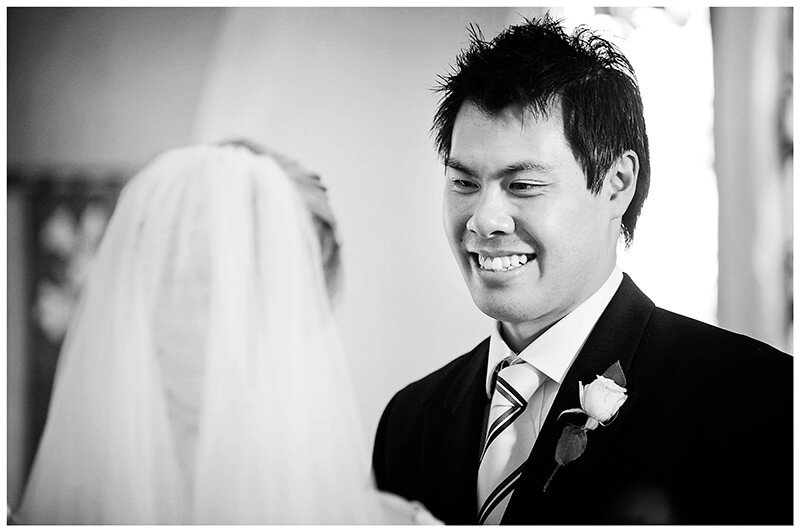 happy groom smiles at bride during multicultural wedding