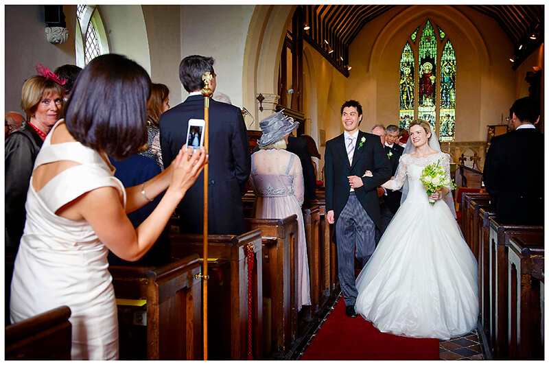 taking a photo of bride and groom as they walk down aisle after multicultural wedding