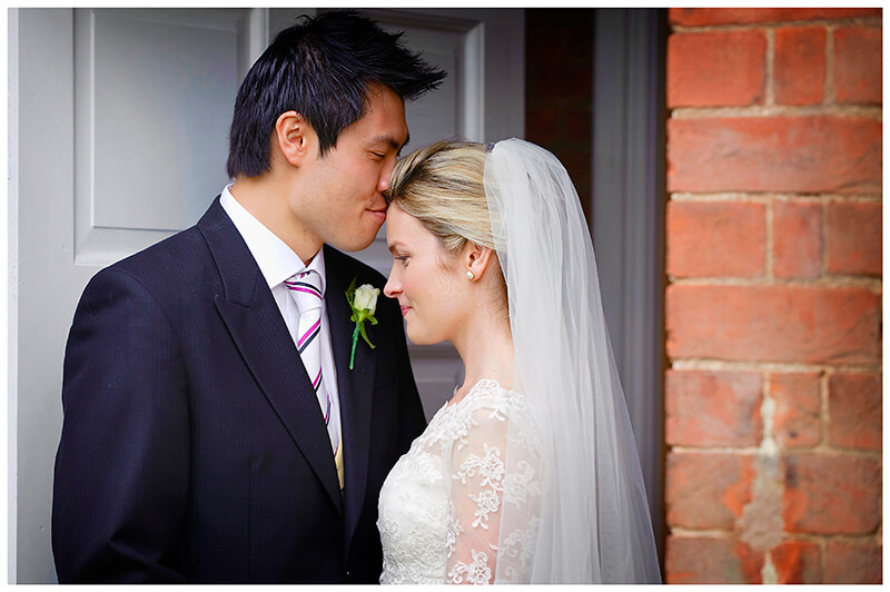 garden wedding in Leicestershire groom kisses bride on fore head as they stand in doorway