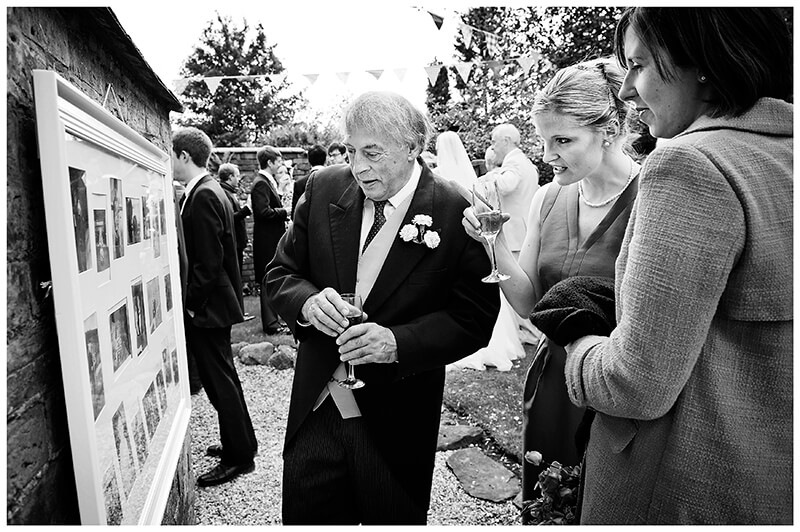 looking at wedding couples history board  during a Garden Wedding reception