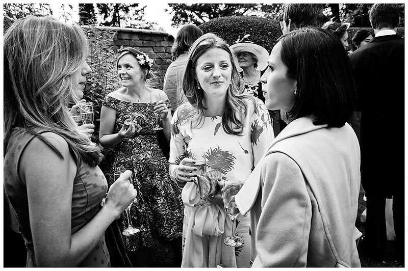 Wedding guests talking enjoying drinks and canapes in a Garden Wedding